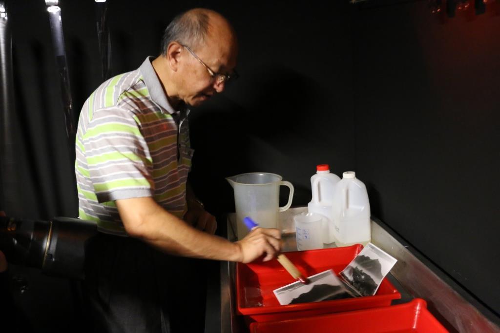 攝影師涂寬裕老師在暗房示範沖洗照片